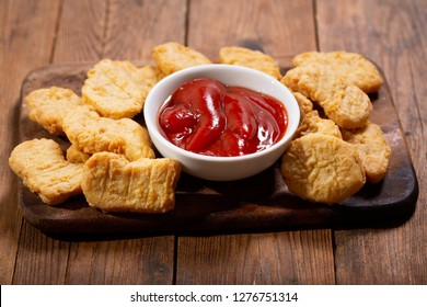 chicken nuggets with ketchup on wooden board