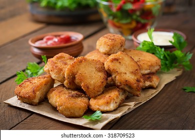 Chicken nuggets and sauce on a wooden background