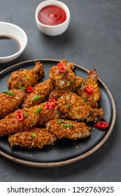 Chicken nuggets with sauce and pepper on a dark background. Copy space.