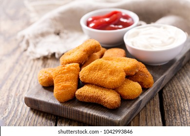 chicken nuggets with sauces on wooden board