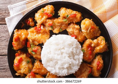chicken in orange sauce with rice close-up on a plate. horizontal view from above