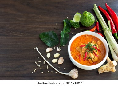 Chicken panang curry in the white bowl and fresh spice on brown wooden background Thai food / Select focus image, and space for message