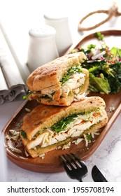 Chicken Panini has Chicken - pesto - mozzarella - rocket - olive panini bread in brown wooden plate, on white background