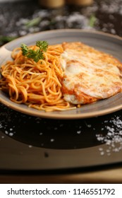 Chicken parmesan with melted cheese served over spaghetti pasta