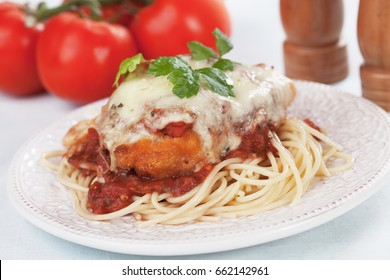 Chicken parmesan with melted cheese and tomato sauce served over spaghetti pasta