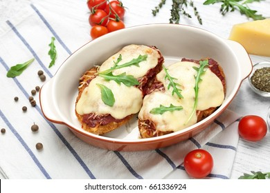 Chicken parmesan with spices in baking dish on table