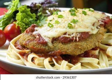 Chicken Parmigiana over fettucine, with a side salad.