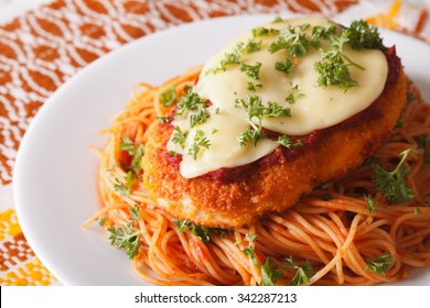 Chicken Parmigiana and pasta closeup on a plate on the table. horizontal