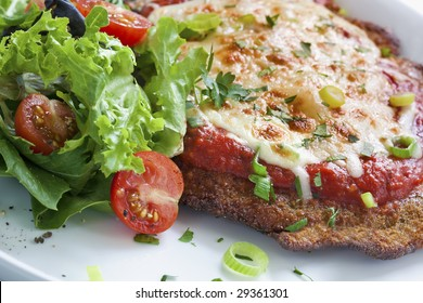 Chicken parmigiana with salad.  Melting parmesan and mozzarella cheeses over an Italian tomato sauce.
