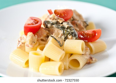 Chicken with pasta and fresh cherry tomatoes on a pastel tablecloth