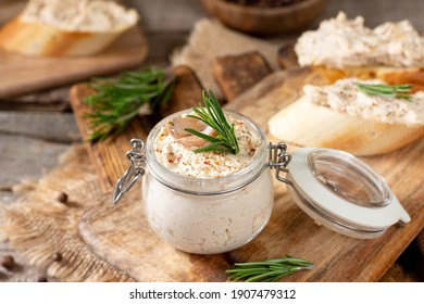 Chicken pate in a glass jar on the brown wooden kitchen table. Homemade chicken fillet pate with seasonings on a wooden background