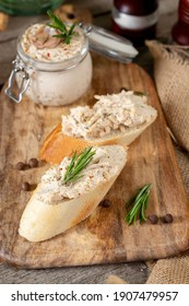 Chicken pate in a glass jar on the brown wooden kitchen table. Baguette slices spread with homemade chicken pate on a serving board