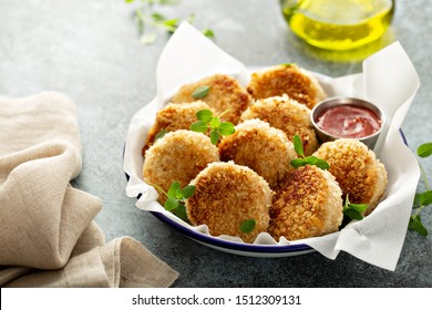 Chicken patties or fish cakes fried in breadcrumbs with ketchup