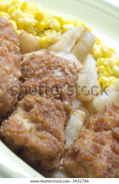 chicken patties strips fried with corn and french fried potatoes