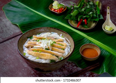 Chicken pho or Pho ga on a table kitchen in Hanoi, Vietnam. Including chicken, fresh rice noodle, herb on broth. Everyday food in Vietnam and famous in the World