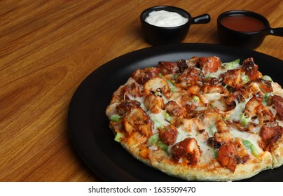 Chicken Pizza or Chicken pan pizza served in black dish on wooden background. Selective focus