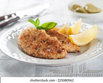 Chicken or pork schnitzel with lemon wedges, selective focus