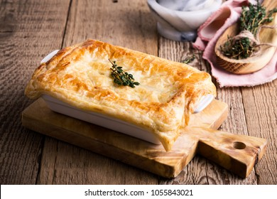 Chicken pot pie with vegetables and aromatic herbs on wooden table.  Traditional american meal in rustic style