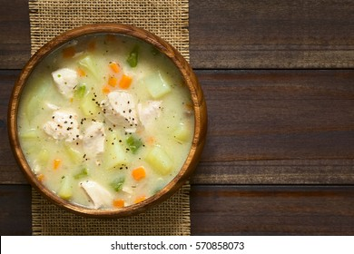 Chicken and potato chowder soup with green bell pepper and carrot in wooden bowl, photographed overhead on dark wood with natural light (Selective Focus, Focus on the soup)