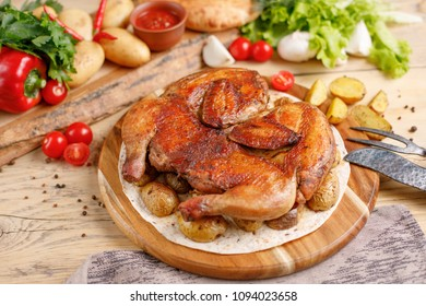 Chicken with potato garnish on a wooden background.Rustic. Still life with textiles and original cutlery.