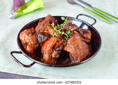 Chicken with prunes cooked in the oven in a black bowl on a textile background.