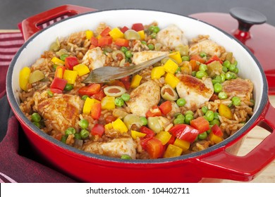 Chicken and rice dish, arroz con pollo, from Latin America, with chicken, rice, beer, tomatoes, capsicums, peas, paprika, cumin, oregano, in a red cast iron casserole.