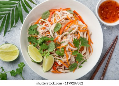 chicken, rice noodle and carrot salad in white bowl with sweet chili sauce, top view