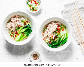 Chicken, rice noodles, boiled chicken, cabbage bok choi, spices soup on white background, top view. Asian style food