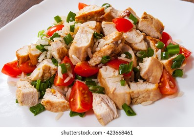 chicken and rice salad with fresh tomatoes in a plate on wooden table