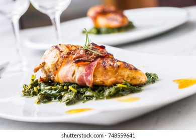 Chicken roasted breast with bacon and spinach on white plate. Culinary food  in hotel pub or restaurant.