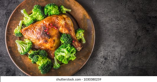 Chicken roasted leg with broccoli on plate.