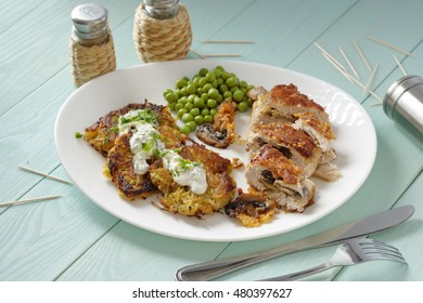 Chicken roll with potato pancakes on a plate.