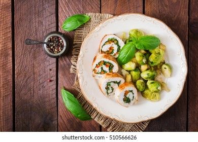 Chicken rolls with greens, garnished with stewed Brussels sprouts, apples and leeks on plate. Top view