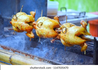 Chicken rotates on the grill.