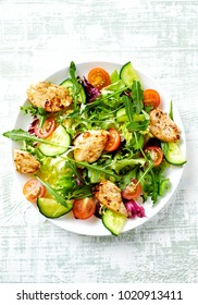Chicken salad with cherry tomatoes, cucumber, endive, radicchio, red onion and fresh rocket. Concept for healthy eating and nutrition. Hand painted wooden background. Top view.