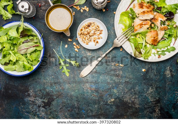 Chicken salad with green mix salad leaves, fork and dressing on rustic background, top view, border. Healthy food and diet eating concept