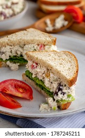 Chicken salad sandwich with lettuce on whole wheat bread sliced in half on a plate