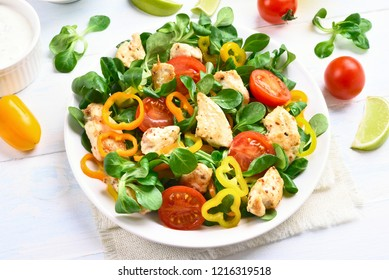 Chicken salad with vegetables in bowl on white wooden table.