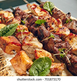 Chicken, Salmon and Meat Shish Kebabs on Parchment with Sauces.