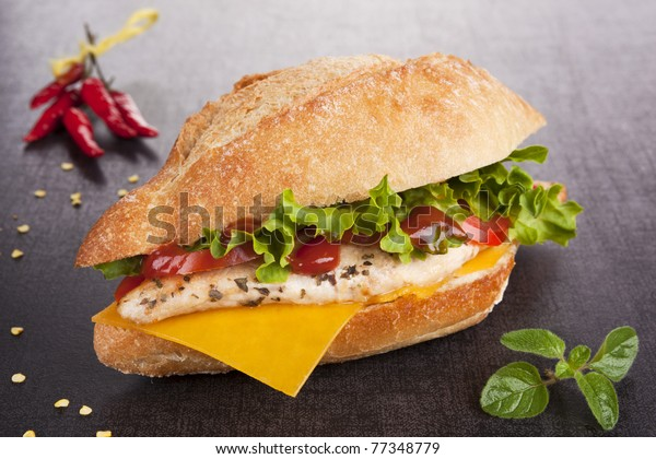 Chicken sandwich with fresh vegetables and cheddar cheese on dark board.