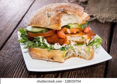 Chicken Sandwich on a plate (wooden background)