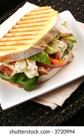 Chicken sandwich on toasted sourdough bread, with avocado, cherry tomatoes, red onion, fetta cheese and lettuce.