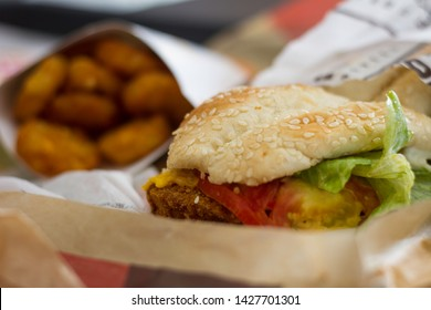 CHICKEN SANDWICH SERVED WITH HASH BROWNS SHOT IN A FAST FOOD RESTAURANT WITH A SHALLOW BACKGROUND