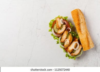 Chicken sandwich with tomato, cucumber, lettuce and onions. White stone background. Top view. Flat lay.