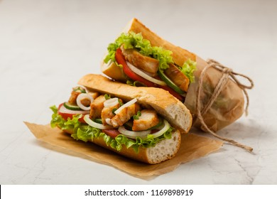 Chicken sandwich with tomato, cucumber, lettuce and onions. White stone background. Front view.