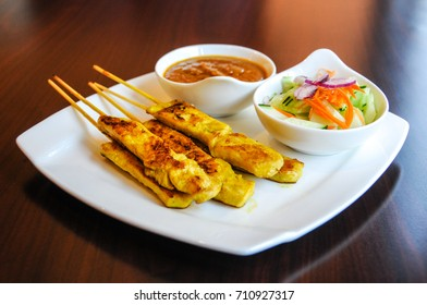 Chicken Satay, Marinated chicken grilled on skewers, served with peanut sauce and cucumber salad.