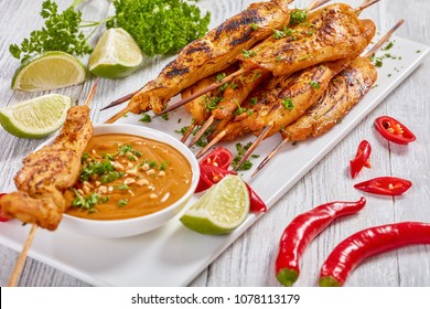 Chicken satay on skewers sprinkled with finely chopped parsley on a white rectangular plate with peanut sauce. red chili peppers, lime slices and parsley at background, view from above, close up
