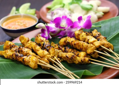 chicken satay, sate ayam and lontong with peanut sauce, indonesian skewer food