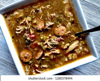 chicken and sausage gumbo in a white square bowl on a wooden table