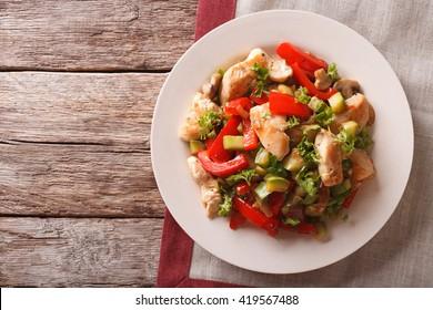 Saute de poulet aux champignons et légumes en gros plan sur une assiette. Vue horizontale du dessus